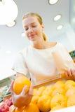 Upward view lady holding orange in shop Royalty Free Stock Image