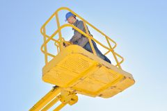 Upward view man in cherry picker. Upward view of man in cherry picker royalty free stock image