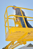 Upward view man in cherry picker bucket. Upward view of man in cherry picker bucket stock image