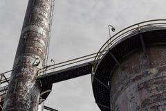Upward view of smoke stacks encircled with walkways against gray skies. Horizontal aspect royalty free stock photos