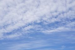 Upward view, wave of softy and white fluffy clouds under deep blue sky stock photos