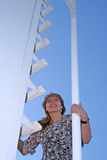 Upwards. Young woman climbing up a ladder Stock Photography