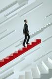 upwards El hombre de negocios sube las escaleras de un vuelo del rojo Imagen de archivo libre de regalías