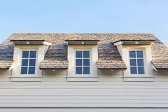 Upwards at 3 home attic windows with roof Royalty Free Stock Photo
