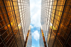 Upwards perspective of symmetrical contemporary skyscrapers, with blue sky and white clouds stock image