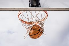 Basketball Swishing Down Through the Net. Upwards shot of a basketball falling through the end of a net. Cloudy, bright skies royalty free stock photo