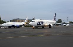 UR-COG YanAir Boeing 737-300 e SP-LLG LOT Polish Airlines Boeing 737-400 aviões na zona de estacionamento imagens de stock royalty free