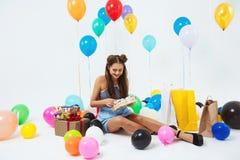 Uradowana dziewczyna odkrywa prezentów urodzinowych pudełka siedzi z helowymi balonami Fotografia Stock