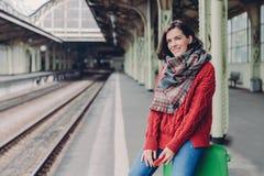 Uradowana młoda Europejska kobieta jest ubranym czerwonego pulower, szalik, chwyta telefon komórkowy, siedzi przy torbą, cieszy s fotografia royalty free