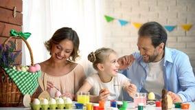 Uradowana rodzina dekoruje Wielkanocnych jajka, szczęśliwy czas wpólnie, trwa wspominki zdjęcie royalty free