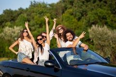 Uradowane eleganckie młode ciemnowłose dziewczyny i faceci w okularach przeciwsłonecznych uśmiechają się w czarnym kabriolecie na zdjęcia royalty free