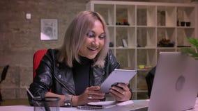 Uradowanej blondynki caucasian kobieta jest uśmiechnięta i swiping jej pastylkę z wielką ciekawą twarzą podczas gdy siedzący w ce