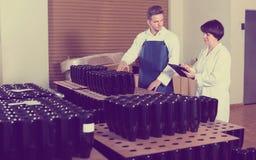 Uradowani pracownicy liczy liczbę wino butelki Zdjęcia Royalty Free