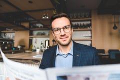 Uradowany mężczyzna patrzeje przez artykułu w kawiarni Fotografia Stock