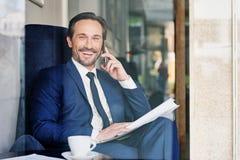 Uradowany męski kierownik używa telefon komórkowego dla komunikaci Zdjęcia Royalty Free