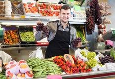 Uradowany męski sprzedawca pokazuje asortyment sklepu spożywczego sklep fotografia stock