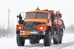 Ural 4320. NOVYY URENGOY, RUSSIA - MARCH 31, 2013: Orange cistern truck Ural 4320 at the city street during a heavy blizzard Stock Image