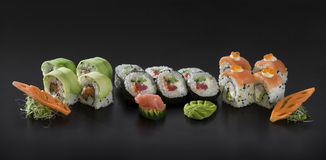 Uramaki and Hosomaki sushi rolls. Fresh Sushi set. Uramaki and Hosomaki sushi rolls over black background Stock Photography
