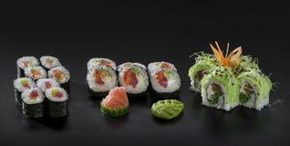 Uramaki and Hosomaki sushi rolls. Mix colorful sushi. Uramaki and Hosomaki sushi rolls over black background Stock Photo