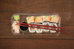 Uramaki and nigiri sushi served with chopsticks and soy sauce in plastic box Royalty Free Stock Image