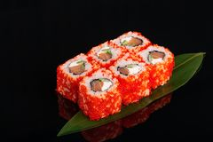 Uramaki philadelphia roll filled with salmon, cucumber, avocado and cream cheese. Philly rolls covered with red flying fish roe stock photography