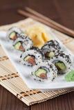 Uramaki sushi with avocado, raw salmon and black sesame. Shallow dof royalty free stock images