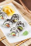 Uramaki sushi with avocado, raw salmon and black sesame. Shallow dof stock image
