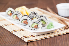 Uramaki sushi with avocado, raw salmon and black sesame. Shallow dof royalty free stock image