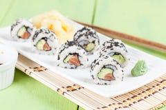 Uramaki sushi with avocado, raw salmon and black sesame. Shallow dof royalty free stock photos