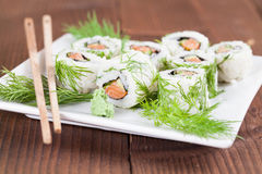 Uramaki sushi with cucumber, raw salmon and dill. Shallow dof royalty free stock photography
