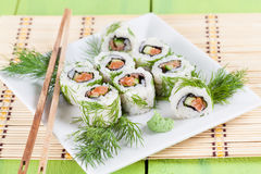 Uramaki sushi with cucumber, raw salmon and dill. Shallow dof royalty free stock image