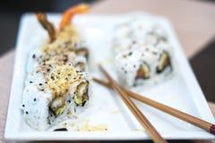 Uramaki sushi rolls with fried shrimp, avocado and philadelphia cheese. A shoot inside a sushi restaurant with 8 uramaki sushi rolls made from rice, fried scrimp Stock Photo