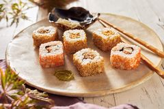 Uramaki sushi rolls on a rustic pottery plate. Uramaki sushi rolls with sesame coating on a rustic pottery plate with chopsticks served as an appetizer in a royalty free stock photo