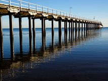 Urangan Pier and Reflection on clear blue skies and sea Stock Photo