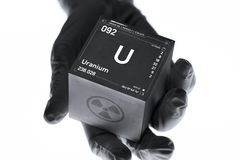 Uranium cube in the hand of a scientist. Radioactive element from the periodic table royalty free stock photography