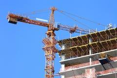 Żuraw i budować w budowie przeciw niebu Zdjęcia Royalty Free