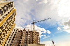 Żuraw i wysoki wzrosta budować w budowie przeciw niebieskiemu niebu Zdjęcia Stock