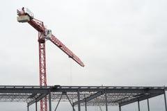 Żuraw na białym chmurnym szarym niebie z budowy struktury metalu architektury przemysłowym budynkiem Zdjęcia Stock