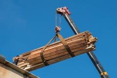 Żuraw podnosi drewniane deseczki na dachu, niebieskie niebo Zdjęcie Stock
