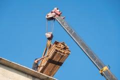Żuraw podnosi drewniane deseczki na dachu, niebieskie niebo Obrazy Stock