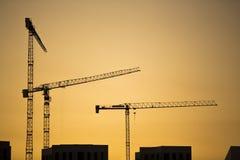 Żurawie przy zmierzchem. Przemysłowi budowa żurawie i budynek sylwetki nad słońcem przy wschodem słońca. obrazy stock