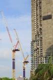Żurawie w budowie z niebieskim niebem i chmurą zdjęcia stock