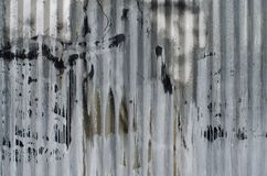 Corrugated metal sheet marked by paint and rust royalty free stock photo