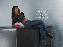 Urban African American woman lying on table. Young ethnic black Afro American in jeans female sitting and leaning on bar countertop table Royalty Free Stock Photography