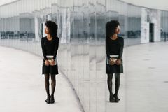 Urban afro hairstyle businesswoman outside. Urban professional stylish businesswoman symmetry reflection outside. Fashionable young black professional woman royalty free stock image