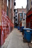 Urban Alley. A dark and atmospheric alleyway with graffiti and trash cans royalty free stock photo