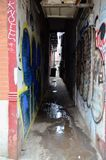 Urban Alley. A dark and atmospheric alleyway with graffiti and waste water stock photo