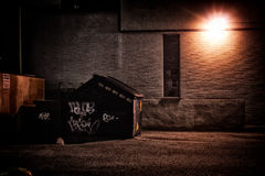 Urban Alley at Night. A dirty, dark, shadowy and dangerous looking urban back-alley at night time with garbage dumpster Stock Photo