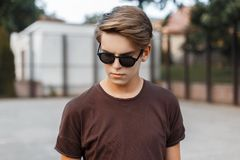 Urban american hipster young man in sunglasses in trendy t-shirt with hairstyle on a modern basketball court outdoors. Attractive handsome guy on vacation stock image