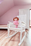 Urban apartment - doll on rocking chair. Urban apartment - pink doll on a white rocking chair Royalty Free Stock Photo